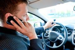 Αρσενικός επιχειρηματίας που μιλά σε ένα τηλέφωνο κυττάρων οδηγώντας Στοκ Εικόνα