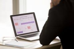 Αρσενικός επιχειρηματίας που σκέφτεται στο πρόγραμμα εργασιών μήνα Στοκ Εικόνες