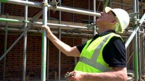 Αρσενικός εργάτης οικοδομών για το εργοτάξιο που επιθεωρεί και που ελέγχει τα υλικά σκαλωσιάς για τις υγείες και ασφάλειες απόθεμα βίντεο