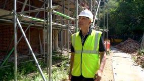 Αρσενικός εργάτης οικοδομών επιστατών οικοδόμων που επιθεωρεί και που ελέγχει τα υλικά σκαλωσιάς για τις υγείες και ασφάλειες απόθεμα βίντεο