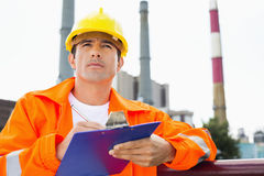 Αρσενικός εργάτης οικοδομών που γράφει στην περιοχή αποκομμάτων στη βιομηχανία Στοκ φωτογραφία με δικαίωμα ελεύθερης χρήσης