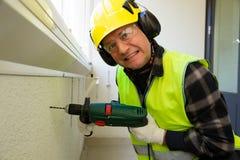 Αρσενικός εργάτης οικοδομών στο σκληρό τρυπώντας με τρυπάνι συμπαγή τοίχο καπέλων Στοκ φωτογραφίες με δικαίωμα ελεύθερης χρήσης