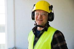 Αρσενικός εργάτης οικοδομών στο σκληρό τρυπώντας με τρυπάνι συμπαγή τοίχο καπέλων Στοκ Εικόνες