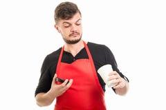 Αρσενικός εργοδότης υπεραγορών που εξετάζει το φλυτζάνι καφέ Στοκ Φωτογραφίες