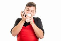 Αρσενικός εργοδότης υπεραγορών που μυρίζει το take-$l*away καφέ Στοκ Εικόνες