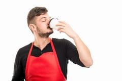 Αρσενικός εργοδότης υπεραγορών που πίνει το take-$l*away καφέ Στοκ Φωτογραφίες
