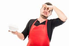Αρσενικός εργοδότης υπεραγορών που το κακό μυρίζοντας καλαθάκι με φαγητό Στοκ Εικόνα