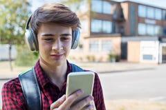 Αρσενικός εφηβικός σπουδαστής έξω από τη μουσική FR ροής οικοδόμησης κολλεγίου στοκ φωτογραφίες