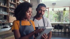 Αρσενικός και θηλυκός ιδιοκτήτης που εργάζεται μαζί στον καφέ απόθεμα βίντεο