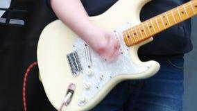 Αρσενικός κιθαρίστας στο σκηνικό παιχνίδι στην ηλεκτρο κιθάρα απόθεμα βίντεο