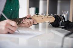 Αρσενικός κιθαρίστας σχετικά με τις σειρές σύροντας τις σημειώσεις Στοκ φωτογραφία με δικαίωμα ελεύθερης χρήσης