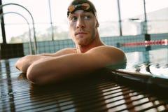 Αρσενικός κολυμβητής που στηρίζεται στην άκρη της πισίνας στοκ φωτογραφία