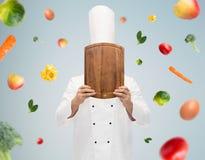 Αρσενικός μάγειρας αρχιμαγείρων που καλύπτει το πρόσωπο με τον τέμνοντα πίνακα Στοκ Εικόνες