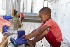 Αρσενικός μαθητής στο σχολείο Montessori που βάζει στις μπότες του Ουέλλινγκτον στοκ φωτογραφία