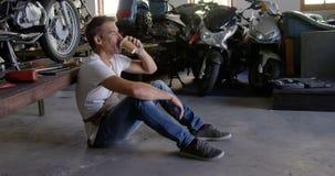 Αρσενικός μηχανικός καφές κατανάλωσης στο γκαράζ 4k επισκευής μοτοσικλετών απόθεμα βίντεο