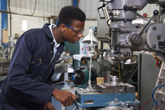 Αρσενικός μηχανικός μαθητευόμενων που εργάζεται στο τρυπάνι στο εργοστάσιο Στοκ Εικόνα