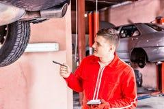 Αρσενικός μηχανικός μηχανών που στέκεται κάνοντας τις σημειώσεις κάτω από ένα ανυψωμένο ασβέστιο Στοκ Φωτογραφία