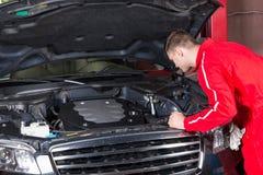 Αρσενικός μηχανικός μηχανών στην ομοιόμορφη μηχανή αυτοκινήτων ελέγχου και καθορισμού Στοκ εικόνα με δικαίωμα ελεύθερης χρήσης