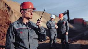 Αρσενικός μηχανικός που δίνει την οδηγία εργασίας που μιλά χρησιμοποιώντας walkie την ομιλούσα ταινία που λειτουργεί στο εργοτάξι φιλμ μικρού μήκους
