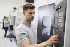 Αρσενικός μηχανικός που ενεργοποιεί cnc τα μηχανήματα στο εργοστάσιο στοκ φωτογραφία με δικαίωμα ελεύθερης χρήσης