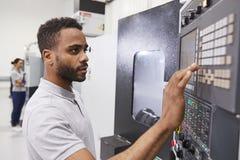 Αρσενικός μηχανικός που ενεργοποιεί cnc τα μηχανήματα στο εργοστάσιο στοκ εικόνες