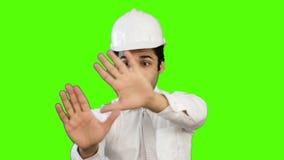 Αρσενικός μηχανικός που παρουσιάζει για το πράσινο υπόβαθρο απόθεμα βίντεο