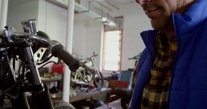 Αρσενικός μηχανικός που χρησιμοποιεί την ψηφιακή ταμπλέτα στο γκαράζ 4k επισκευής μοτοσικλετών απόθεμα βίντεο