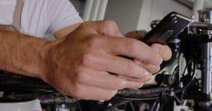 Αρσενικός μηχανικός που χρησιμοποιεί το κινητό τηλέφωνο στο γκαράζ 4k επισκευής μοτοσικλετών απόθεμα βίντεο