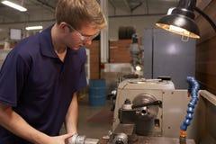 Αρσενικός μηχανικός στο εργοστάσιο που χρησιμοποιεί τη μηχανή άλεσης Στοκ εικόνες με δικαίωμα ελεύθερης χρήσης