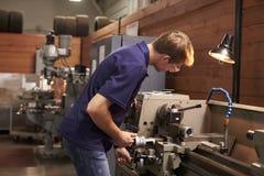 Αρσενικός μηχανικός στο εργοστάσιο που χρησιμοποιεί τη μηχανή άλεσης Στοκ Εικόνα