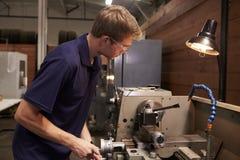 Αρσενικός μηχανικός στο εργοστάσιο που χρησιμοποιεί τη μηχανή άλεσης Στοκ εικόνα με δικαίωμα ελεύθερης χρήσης