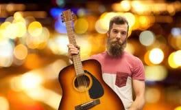Αρσενικός μουσικός με την κιθάρα πέρα από τα φω'τα πόλεων νύχτας Στοκ Εικόνες