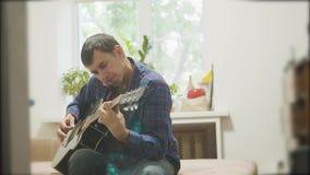 αρσενικός μουσικός που παίζει την ακουστική κιθάρα άτομο που παίζει το ακουστικό βίντεο τρόπου ζωής κιθάρων σε αργή κίνηση στο δω απόθεμα βίντεο