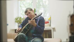 αρσενικός μουσικός που παίζει την ακουστική κιθάρα άτομο που παίζει το ακουστικό σε αργή κίνηση βίντεο κιθάρων στο δωμάτιο ο τρόπ απόθεμα βίντεο