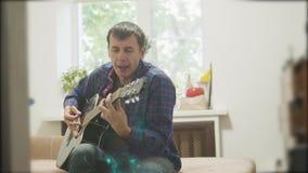 αρσενικός μουσικός που παίζει την ακουστική κιθάρα τρόπος ζωής ατόμων που παίζει το ακουστικό σε αργή κίνηση βίντεο κιθάρων στο δ απόθεμα βίντεο