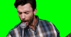 Αρσενικός μουσικός που τραγουδά παίζοντας την κιθάρα απόθεμα βίντεο
