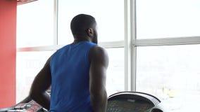 Αρσενικός μπόξερ αφροαμερικάνων που τρέχει treadmill και που ασκεί στη γυμναστική φιλμ μικρού μήκους
