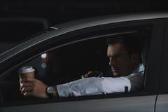 αρσενικός μυστικός αξιωματούχος με το φλιτζάνι του καφέ εγγράφου που χρησιμοποιεί την ομιλούσα ταινία walkie στοκ εικόνες