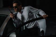 αρσενικός μυστικός αξιωματούχος στα γυαλιά ηλίου που χρησιμοποιούν την ομιλούσα ταινία walkie στοκ εικόνες