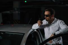 αρσενικός μυστικός αξιωματούχος στα γυαλιά ηλίου που χρησιμοποιούν την ομιλούσα ταινία walkie στοκ εικόνες με δικαίωμα ελεύθερης χρήσης