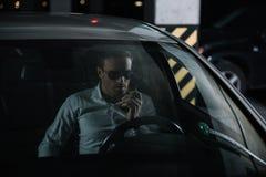 αρσενικός μυστικός αξιωματούχος στα γυαλιά ηλίου χρησιμοποιώντας την ομιλούσα ταινία walkie και καθμένος στοκ εικόνες