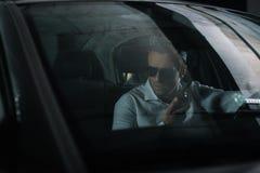 αρσενικός μυστικός αξιωματούχος χρησιμοποιώντας την ομιλούσα ταινία walkie και κατασκοπεύοντας στοκ εικόνα