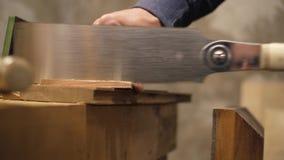 Αρσενικός ξυλουργός που πριονίζει το ξύλινο στοιχείο με ένα πριόνι χεριών 4K απόθεμα βίντεο