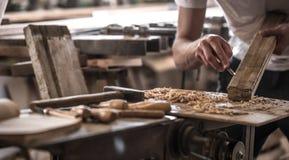 Αρσενικός ξυλουργός που εργάζεται με ένα ξύλινο προϊόν, εργαλεία χεριών Στοκ Φωτογραφίες