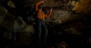 Αρσενικός οδοιπόρος που εξερευνά μια σκοτεινή σπηλιά 4k απόθεμα βίντεο