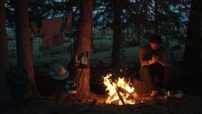 Αρσενικός οδοιπόρος που στηρίζεται κοντά στη φωτιά στο δασικό στρατόπεδο υπαίθρια αναψυχή απόθεμα βίντεο