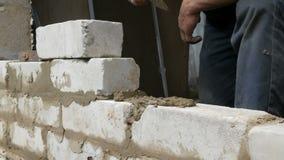 Αρσενικός οικοδόμος που βάζει το άσπρο τούβλο στο τσιμέντο και που στέκεται τον τοίχο Τα χέρια του ατόμου που βάζει τα τούβλα οικ απόθεμα βίντεο