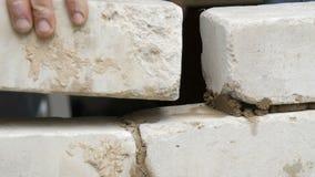 Αρσενικός οικοδόμος που βάζει το άσπρο τούβλο στο τσιμέντο και που στέκεται τον τοίχο Τα χέρια του ατόμου που βάζει τα τούβλα οικ φιλμ μικρού μήκους