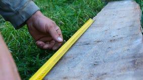 Αρσενικός οικοδόμος που παίρνει τις μετρήσεις του ξύλινου πίνακα με μια μετρώντας ταινία ή ένα κριτήριο φιλμ μικρού μήκους