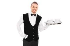 Αρσενικός οικονόμος που κρατά έναν δίσκο με δύο φλιτζάνια του καφέ στοκ φωτογραφία